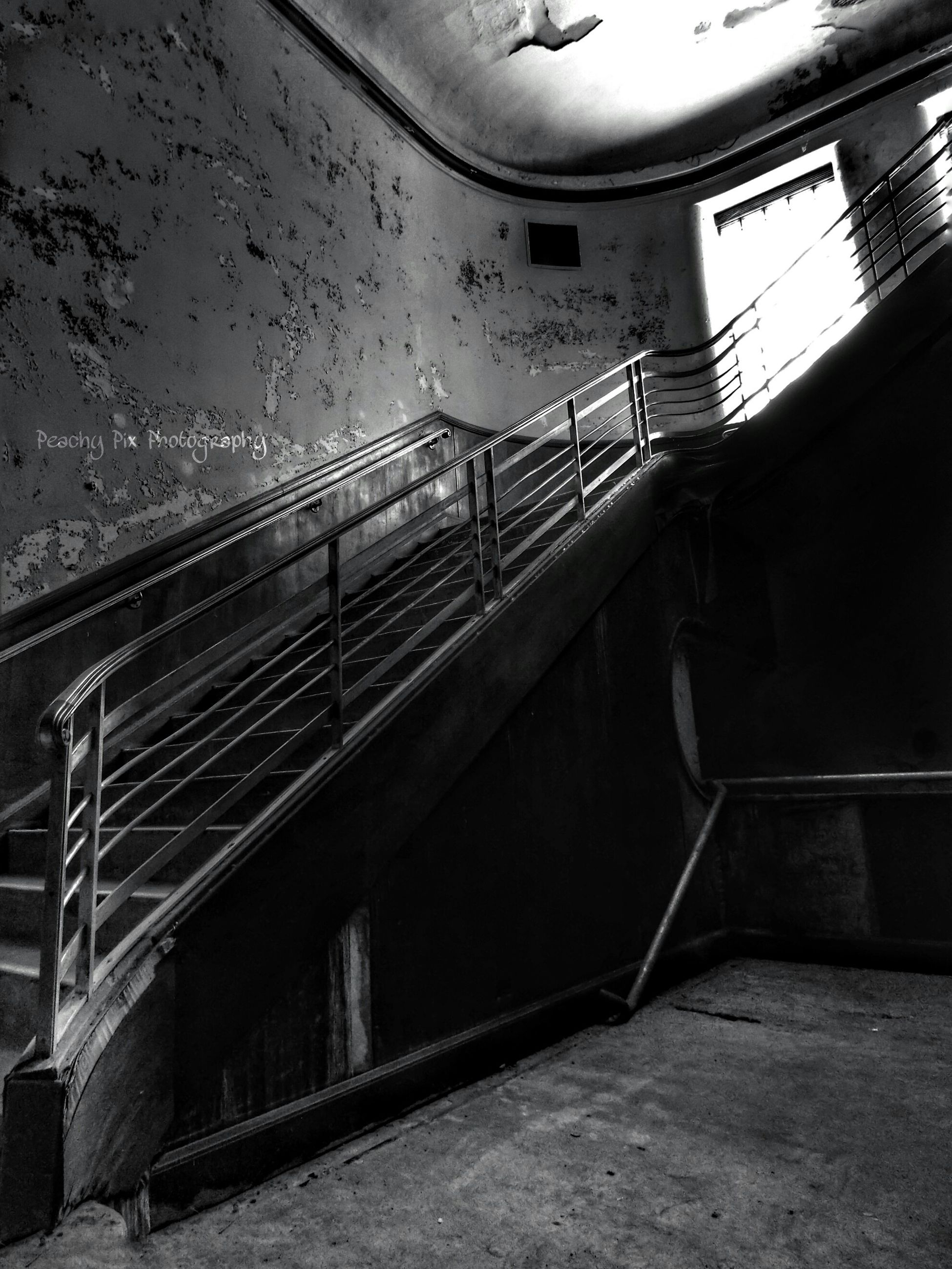 indoors, built structure, architecture, railing, steps, ceiling, staircase, steps and staircases, empty, illuminated, transportation, the way forward, absence, connection, rail transportation, railroad station, metal, no people, diminishing perspective, high angle view