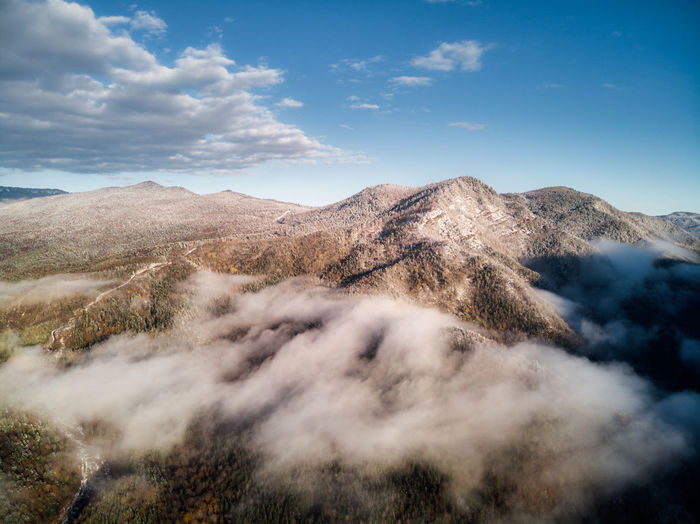 Aerial view, sea of fog and clouds illuminated by the rising sun, snow on the tops of the mountains