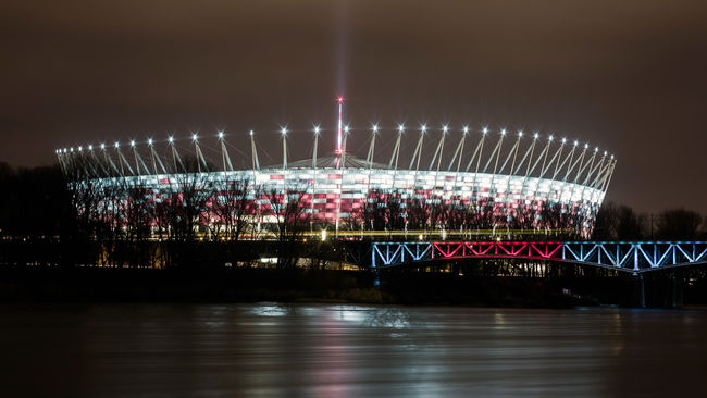 National Stadium in Warsaw Illuminated Night Architecture Water Built Structure Sky Reflection No People Arts Culture And Entertainment Nature Waterfront River Long Exposure Motion Outdoors Amusement Park Amusement Park Ride Blurred Motion Glowing Nightlife Warsaw Legia Poland National Stadium Stadion Narodowy