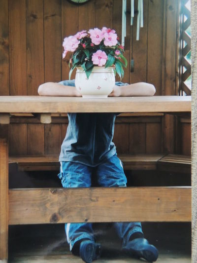 Boy behind vase on table