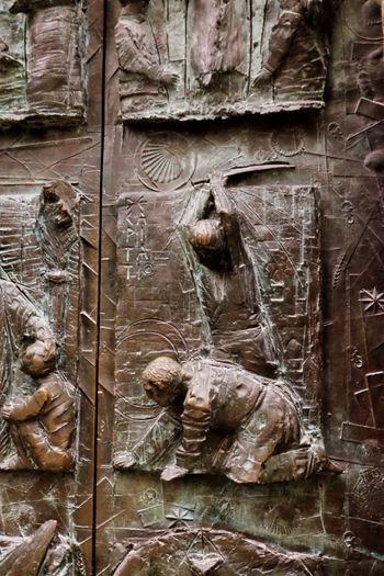 Ancient door depicting various scenes inside the Cathedral Cathedral Christianity Beheading Metal Full Frame Craft Carving - Craft Product No People Day Backgrounds The Past Representation