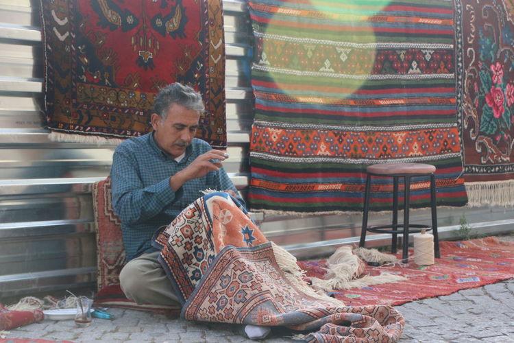 Man preparing carpet while sitting on footpath