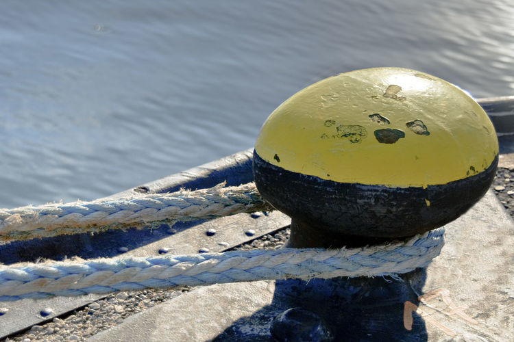 Bollard Close-up Day Focus On Foreground High Angle View Inflatable  Mode Of Transportation Nature Nautical Vessel No People Outdoors Post Protection Rope Safety Sea Security Strength Sunlight Transportation Water