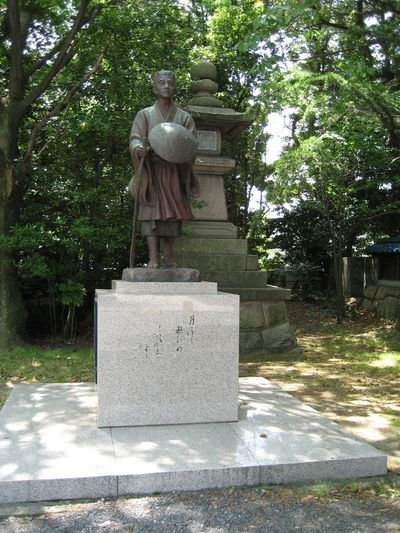 Statue of Matsuo Basho, the most famous poet of the Edo period in Japan. He wrote Oku no Hosomichi (Narrow Road to the Interior) which is considered to be one of the major texts of classical Japanese literature. At the base of the statue the following (from Oku no hosomichi) is written: 月清し遊行の持てる砂の上 Japan Matsuo Basho Walking Stick Wandering Classical Literature Edo Period Haiku Haiku Poem Human Representation Literature Male Likeness No People Outdoors Poet Poetry Statue Straw Hat Zori