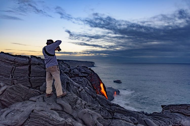 Man Photographing Volcanic Eruption By Sea During Sunrise