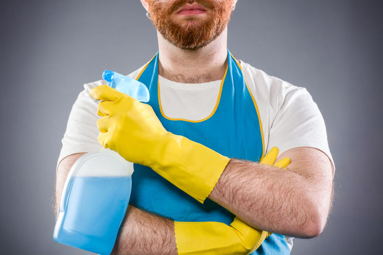 Midsection of man holding spray bottle
