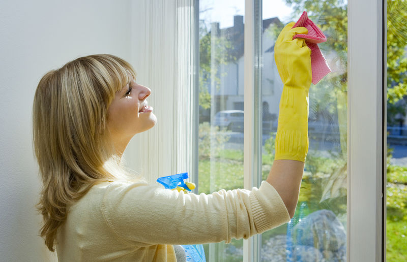 Side View Of Smiling Mid Adult Woman Cleaning Window At Home
