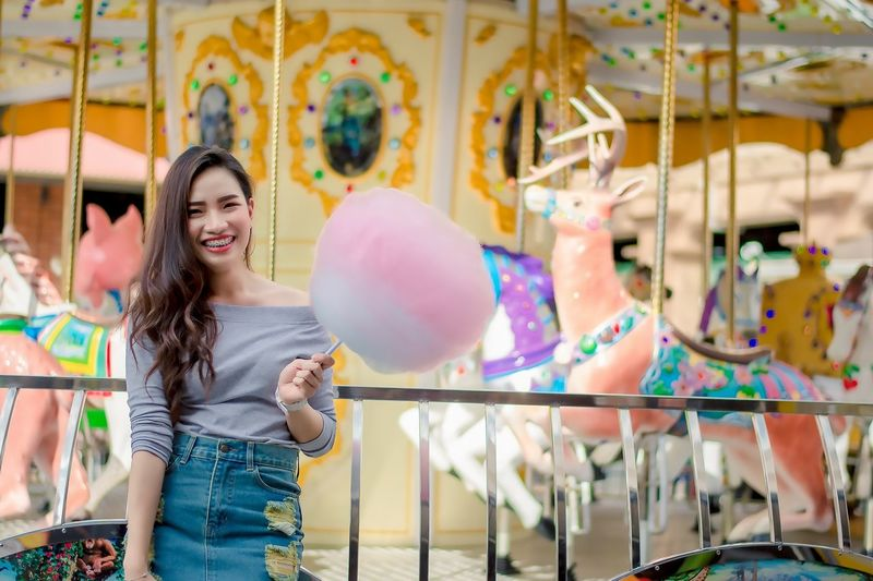 Portrait of cheerful woman standing at amusement park