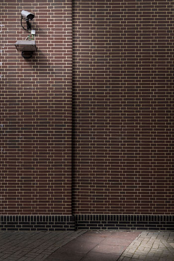 Security camera on brick wall of building