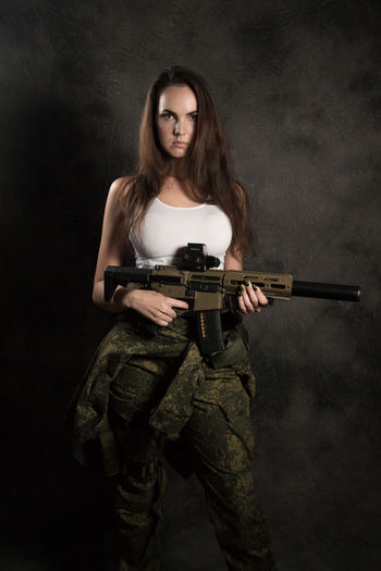 Adult Beautiful Woman Black Background Clothing Front View Full Length Government Gun Hairstyle Holding Indoors  Long Hair Looking At Camera Military One Person Portrait Rifle Standing Studio Shot Uniform Weapon Young Adult