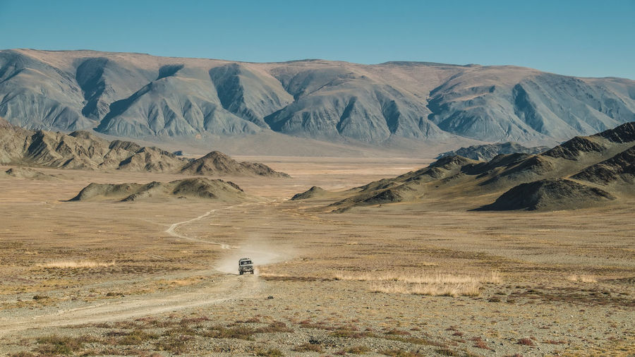 Jeep driving through the vast landscape of Mongolia Central Asia Mongolia All Terrain Vehicle Arid Climate Beauty In Nature Day Desert Environment Idyllic Jeep Land Landscape Mountain Mountain Range Nature Nomads Non-urban Scene Outdoors Remote Scenics - Nature Sky Tranquil Scene Tranquility Travel
