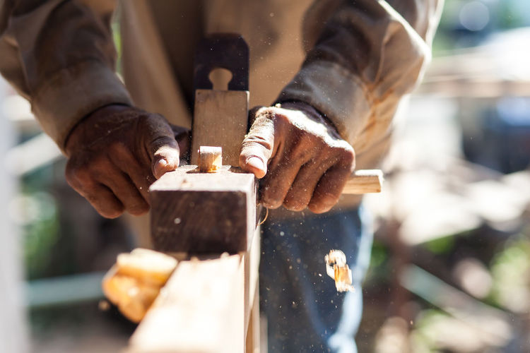 Midsection of carpenter using plane on wood
