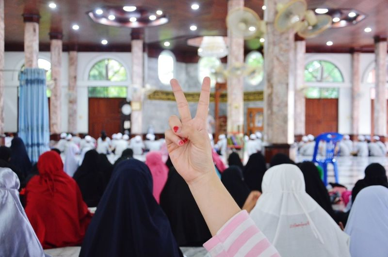 Hand showing peace sign in mosque