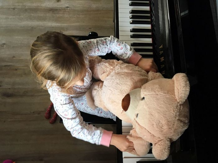 Directly above shot of girl with teddy bear playing piano at home