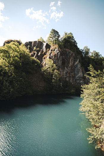 Scenic view of cliff by trees against sky