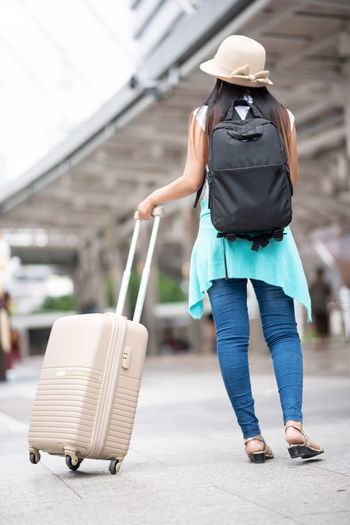 Full Length One Person Walking Luggage Focus On Foreground Women Rear View Casual Clothing Suitcase Real People Travel Clothing Day Adult Transportation Hat Lifestyles Mid Adult Women Standing Outdoors Hairstyle