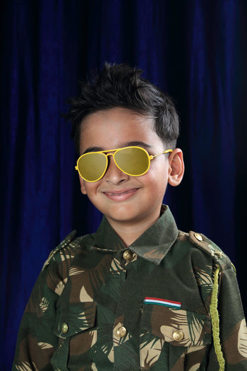 Portrait of smiling boy in army uniform and sunglasses standing against curtain