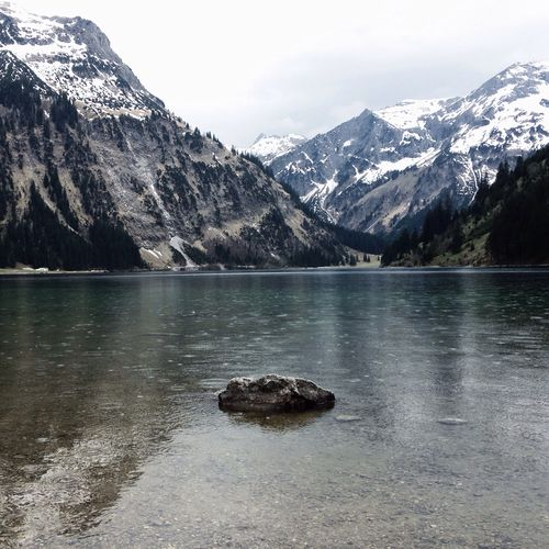 Lake between snowy mountains with a rock  standing in the middle of water