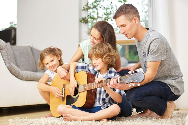 Family Playing Guitar At Home