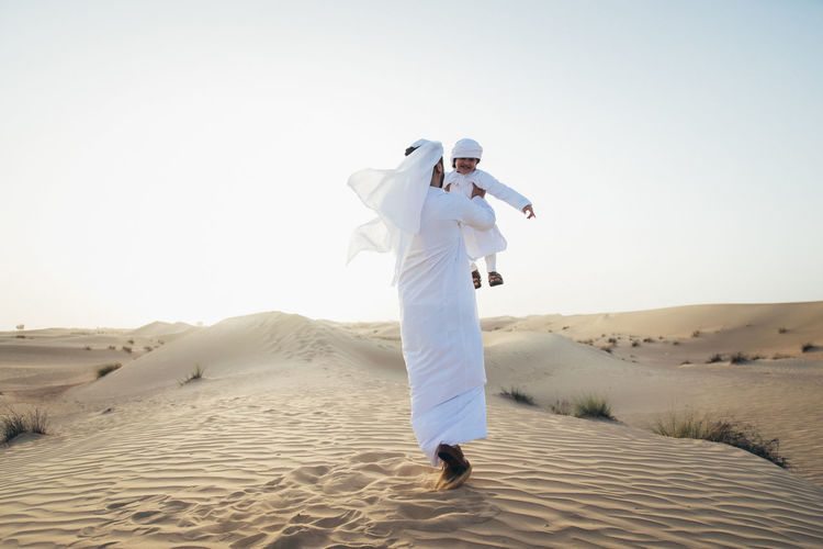 Smiling father and son enjoying while standing in desert