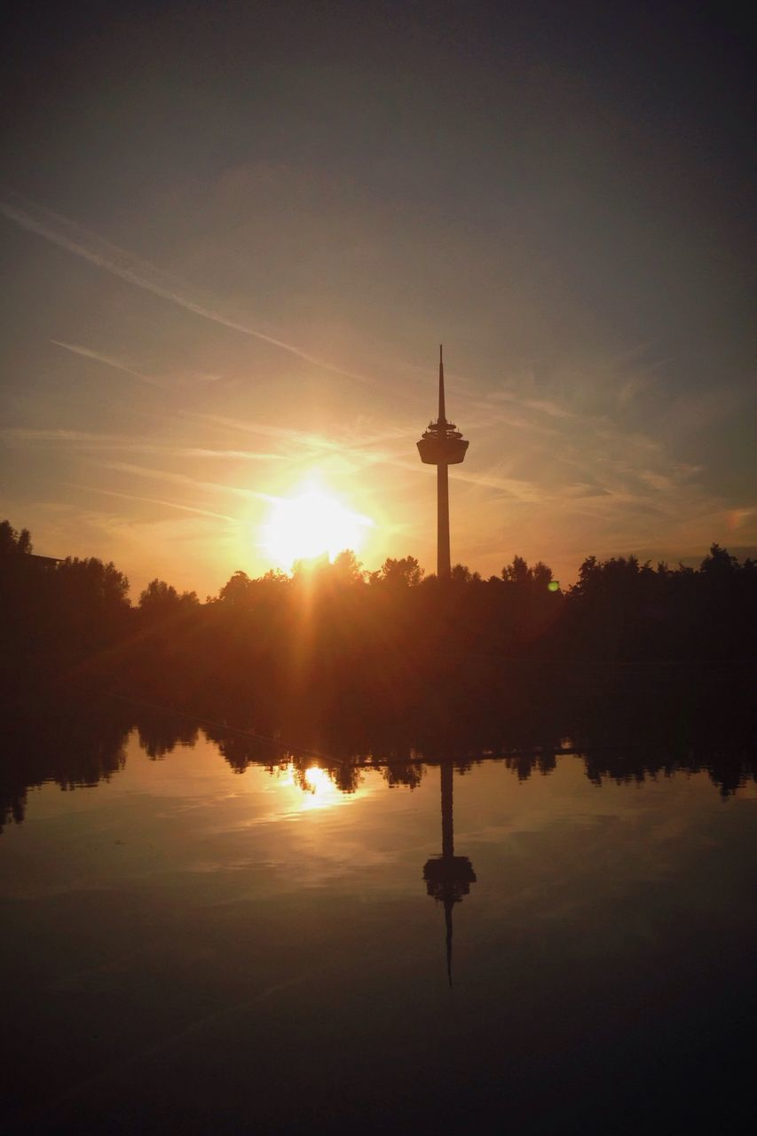 Reflection Of Communication Tower In Lake During Sunset