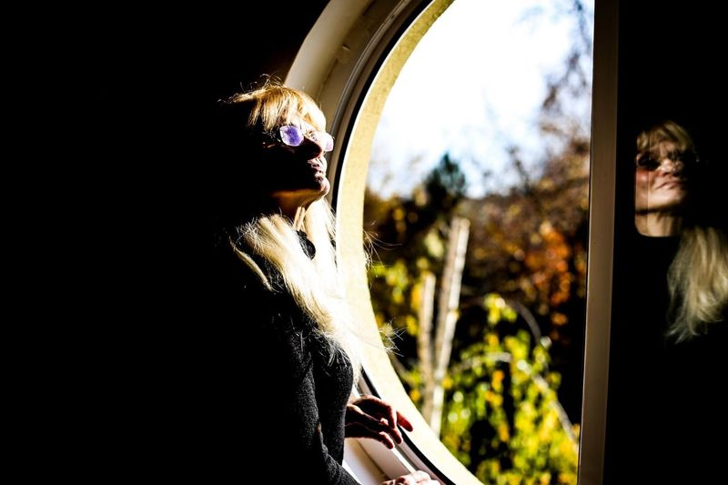 Senior Woman Wearing Sunglasses While Standing By Window