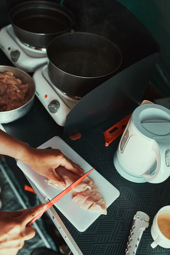 Woman preparing food for dinner in camping kitchen using camping cookers and pots