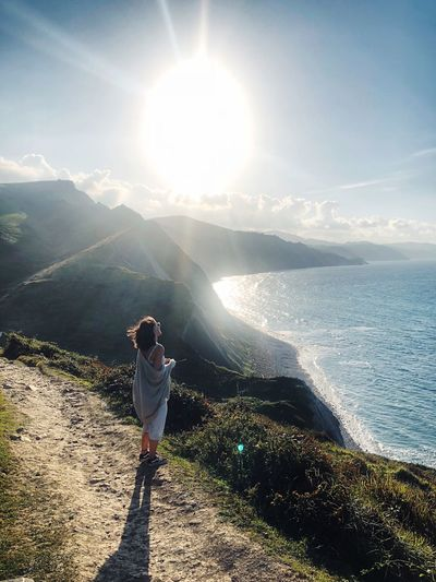 Full length of woman looking at sea against sky on sunny day