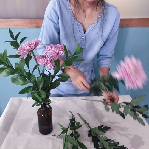 Midsection Of Woman Arranging Flowers In Vase At Home