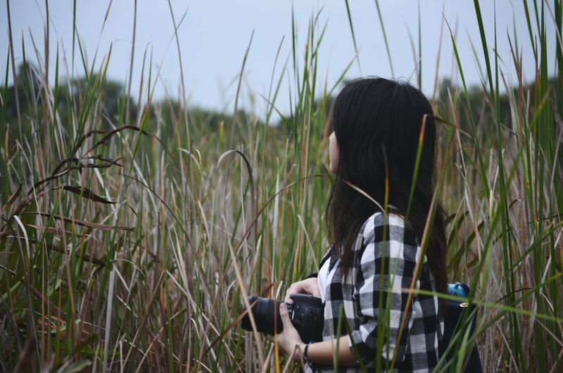 Young woman with camera standing on grassy field
