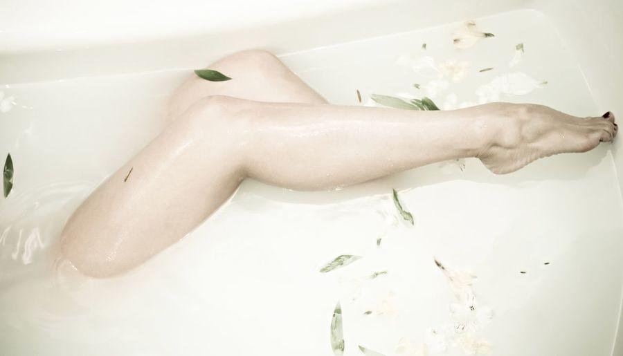 Low section of woman taking milkbath in bathtub