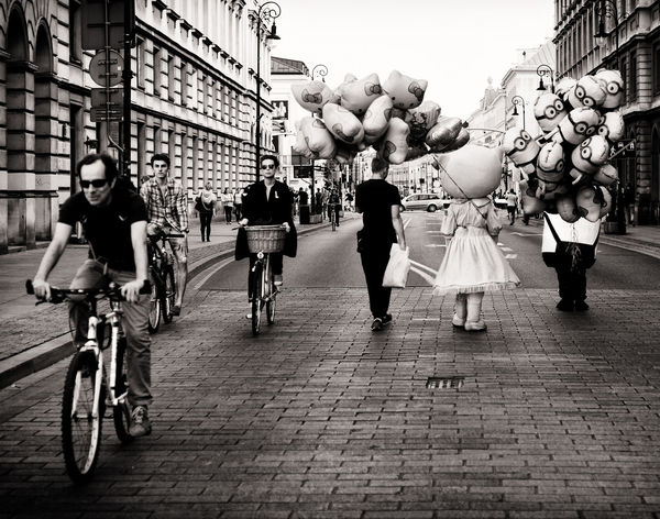 Adult Architecture Bicycle Building Exterior Built Structure City City Life Day Full Length Large Group Of People Lifestyles Men Outdoors People Real People Street Women The Street Photographer - 2017 EyeEm Awards EyeEmNewHere Street Photography Street Vendors Baloons