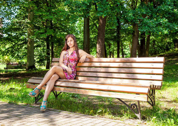 Full length of young woman sitting on bench at park