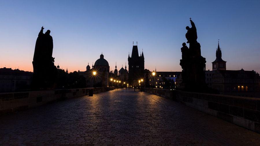Charles bridge against sky in city at dusk