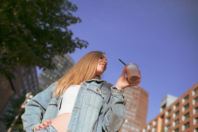 Woman holding disposable cup in city