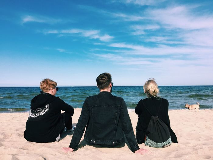 Rear View Of Young Friends Sitting At Beach Against Sky