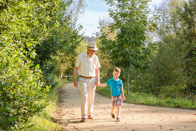 Grandfather and grandson holding hands while walking at park