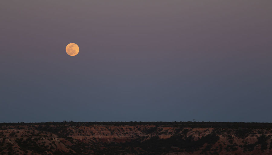 Full moon over landscape at dusk