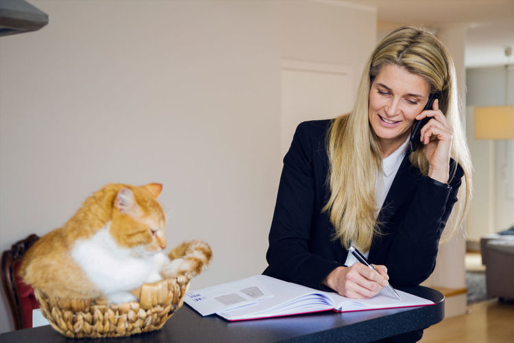 Mature Businesswoman Using Mobile Phone While Writing In Book By Cat Sitting In Basket At Home