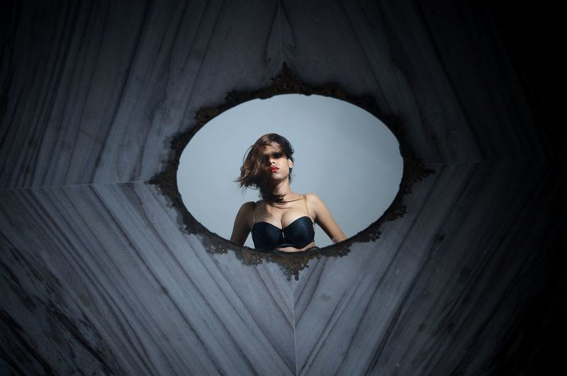 Portrait of young woman wearing bra while reflecting on mirror