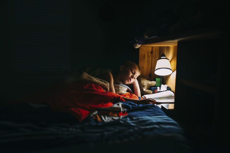 Man using mobile phone while sitting on bed at home