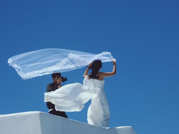Wedding Dress Wedding Photography Wehender Schleier Flying Veil White And Blue Colour Santorini ägäis Aegean Islands Greece Imerovigli Hochzeitskleid Wedding Dress Honeymoon Island Honeymoon Destination Blue Sky Clear Sky Low Angle View Adults Only Full Length Young Adult People