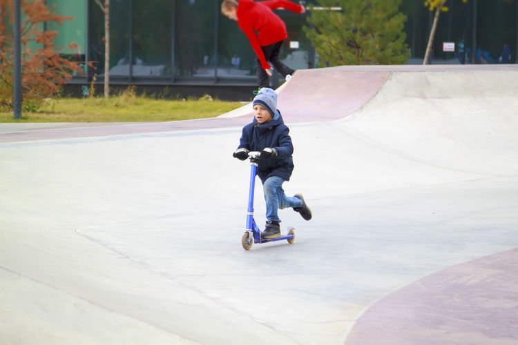 Full length of boy on push scooter