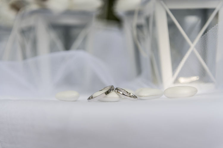 Close up of Wedding rings near comfits and wedding favors No People Selective Focus Close-up Still Life Indoors  Wedding Ring Emotion Love Jewelry Celebration Wedding Ring Event Life Events Positive Emotion Table White Color Metal Focus On Foreground Wealth Personal Accessory Luxury