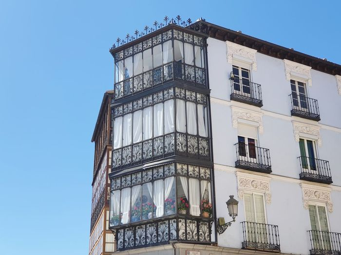 Low angle view of building against clear blue sky. ornamental steel balcony in segovia.