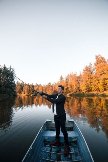 Man standing by lake against sky during autumn