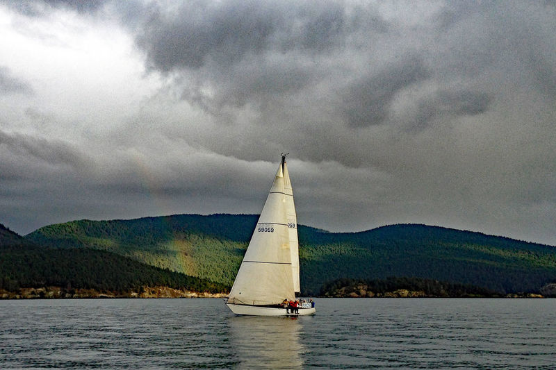 Easy reach Alone In Nature Forest Background Gathering Clouds Wilderness Outdoors Rainbow Vulnerability  Dark Clouds Weather Condition Calm Water Surface Adventure Islands Explore Nature Sails Incedental People Outdoor Activities Mountain Background Inland Sea Weekend Activities Coastal Landscape Liesure Activity Sailing Bay Of Water Transportation Nature Yachting Beauty In Nature Environment Canvas Sport