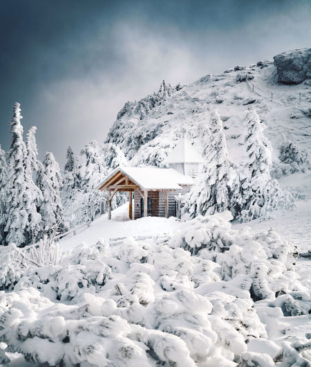 White house on snow covered mountain against sky