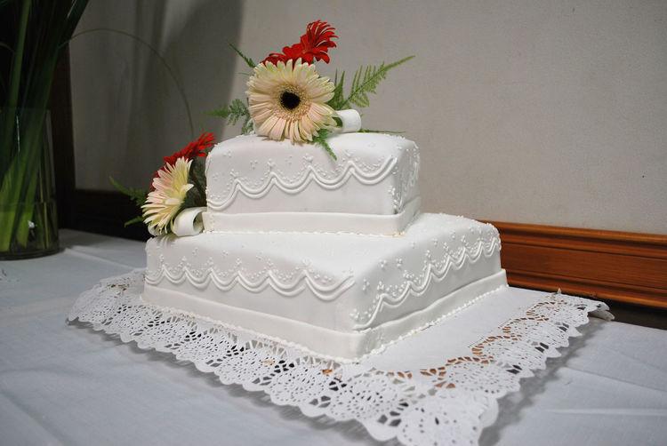 Flower over cake on table against white wall
