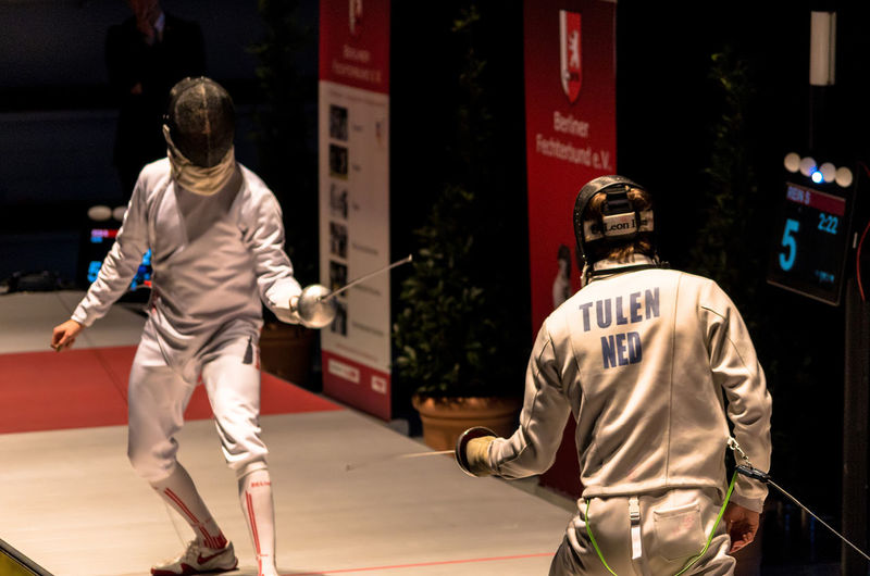 """Two male fencer at the """"White Bear of Berlin"""", a yearly fencing sport event of superlatives in Berlin, Germany on January 14th, 2018. Professional Sport Team Sport Uniform Males  Action Practicing Stadium USA Athlete Sports Uniform Competition Playing Competitive Sport Sport Only Men People Adult Adults Only Competition Outdoors Day Real People Text Two People Men Love Yourself #FREIHEITBERLIN"""
